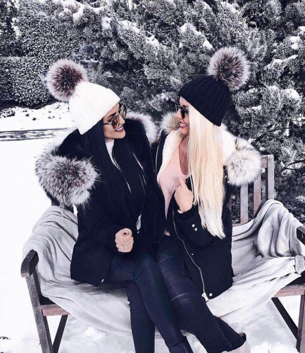 Mujer de cabello negro y mujer de cabello rubio sentadas en una banca en la nieve con ropa que combina