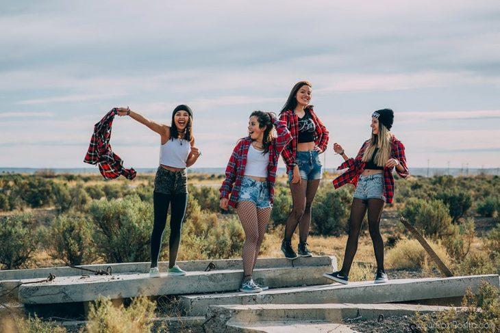 Cuatro mujeres en la naturaleza con shorts y camisas de cuadros rojos que combinan
