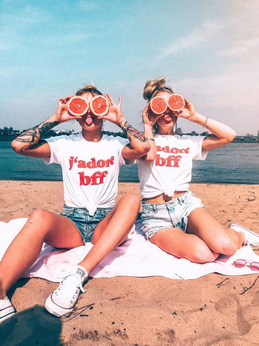 Mujeres rubias en la playa con toronjas usando ropa que combina