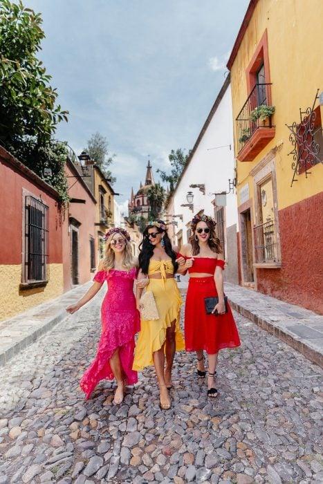 Mujeres caminando con ropa que combina y corona de flores por una calle empedrada