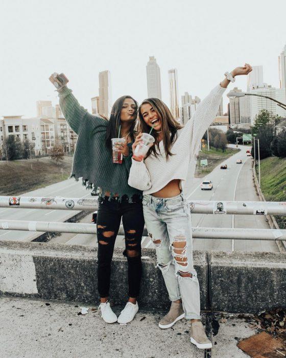 Chicas de cabello castaño en un puente bebiendo té helado con ropa que combina