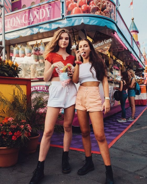 Mejores amigas en la feris comiendo algodón de azúcar usando ropa que combina