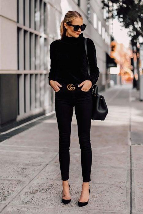 Chica por la calle luciendo un traje negro en tacones y cinturón dorado