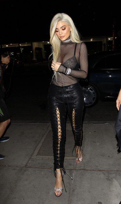 Kyle Jenner paseando por la calle con pantiblusa transparente y leggins de piel negros
