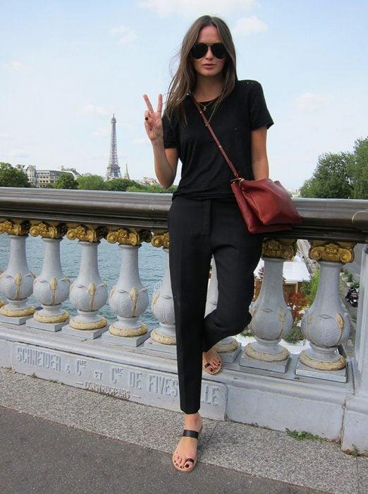 Chica posando con un atuendo negro, sandalias negras y bolso rojo quemado