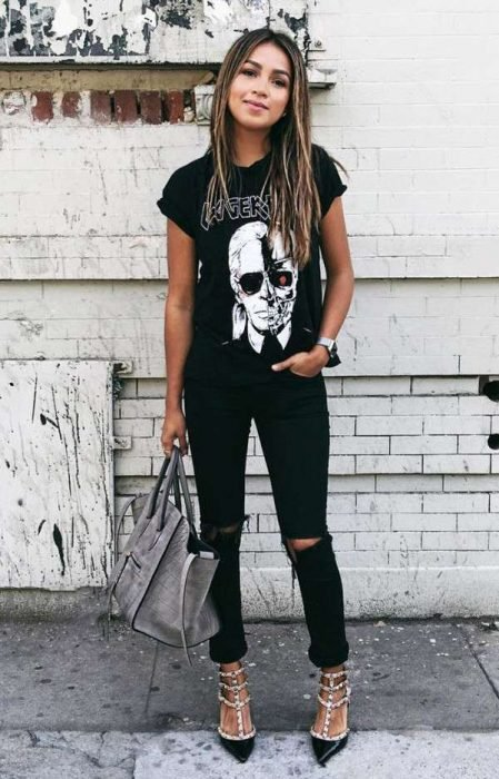 Chica modelando un pantalón negro y blusa con estampado y stilettos