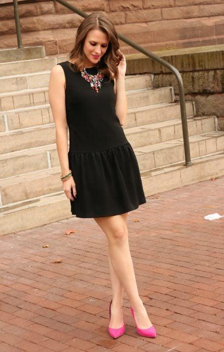 Chica cerca de unas escaleras con vestido negro y calzado rosa
