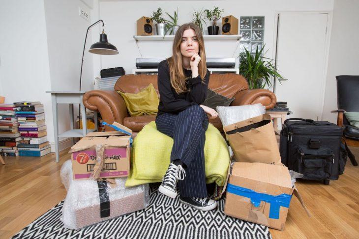 Vicky Spratt, chica que sufrió efectos secundarios de pastillas anticonceptivas sentada en un sillón rodeada de libros y cafas