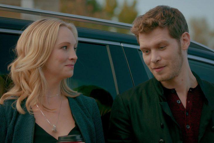 Pareja rubia de novios sonriendo recargados en un auto