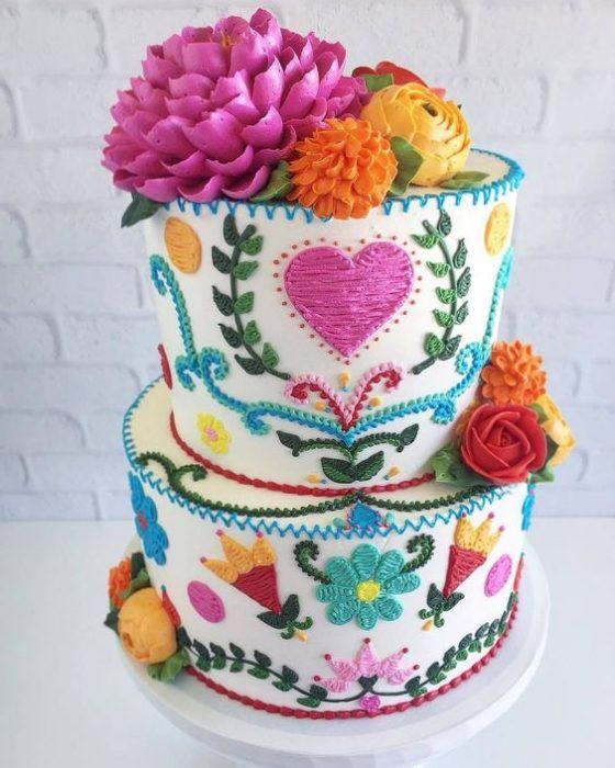 Pastel mediano decorado con betún en efecto bordado con corazones, flores y estrellas