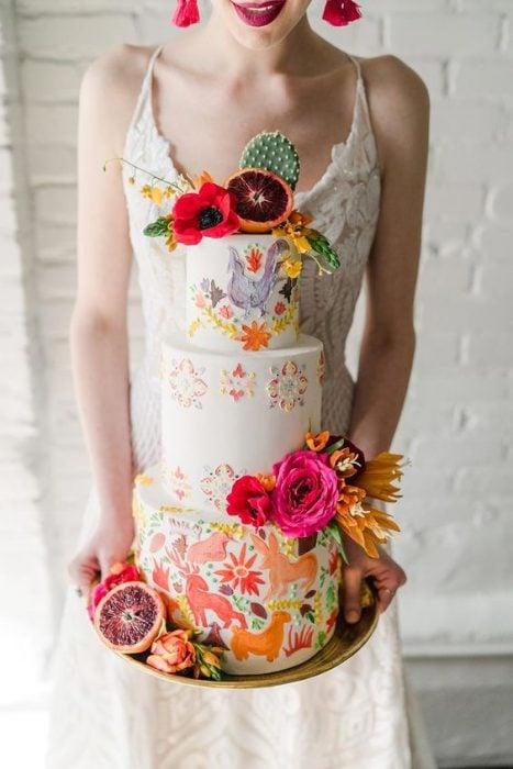Mujer sosteniendo un pastel de tres pisos con betún de vainilla blanco y decorado con flores naturales de colores