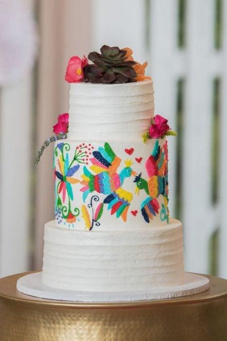 Pastel para boda de tres pisos decorado con betún en color blanco y detalles con efecto bordado de aves
