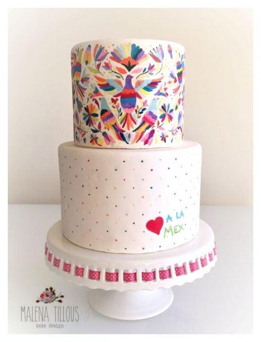 Pastel para cumpleaños de dos pisos con efecto bordado estilo mexicano en colores azul, morado, rojo, naranja y amarillo