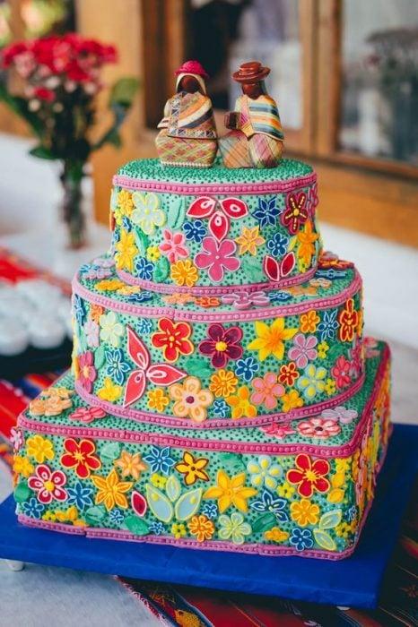 Pastel con base rectangular y dos pisos circulares decorado con efecto bordado de flores en tonos amarillo, verde, guinda, rosa, rojo y amarillo