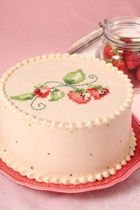 Pastel decorado con betún clássico y figuras en efecto de bordado con punto de cruz en tonos rojo y verde