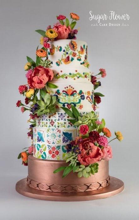 Pastel de tres pisos sobre base de cobre, decorado con flores naturales y de betún clásico sabor vainilla
