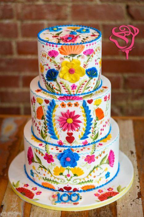 Pastel de tres pisos decorado con efecto bordado, flores de colores rosa, amarillo, azul, naranja y puntos en todos fluorescentes