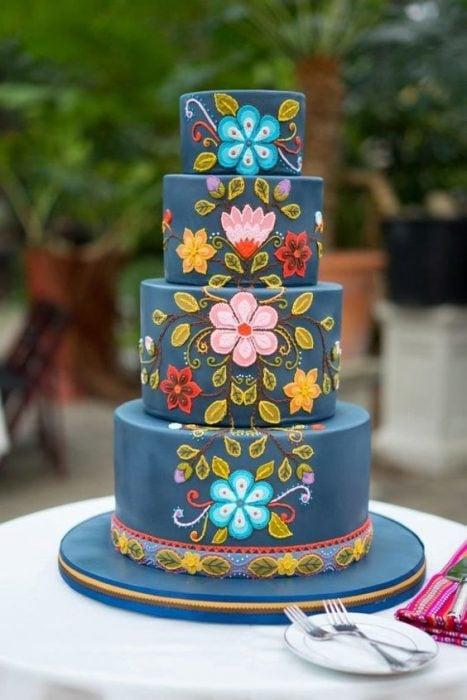 Pastel de tres pisos con betún en color azul marino y decorado de en flores de colores simulando tejido