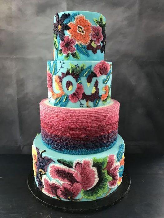 Pastel de cuatro pisos, con fondo en betún color aqua y decorado con efecto bordado en flores y aves