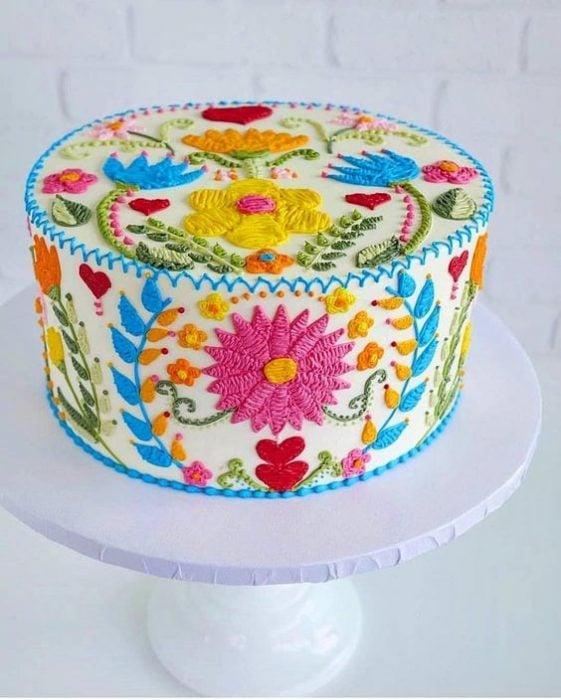 Pastel clásico decorado con efecto bordado con flores en tonos rosa, naranja, azul, amarillo, rojo y rosa