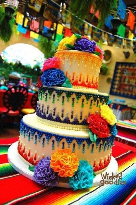 Pastel de tres pisos decorado coon betún en colores azul, verde, amarillo, naranja y rojo