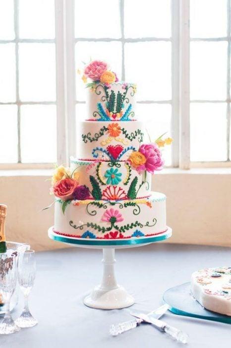 Pastel de tres pisos para boda, decorado con flores y detalles en efecto bordado, estilo mexicano