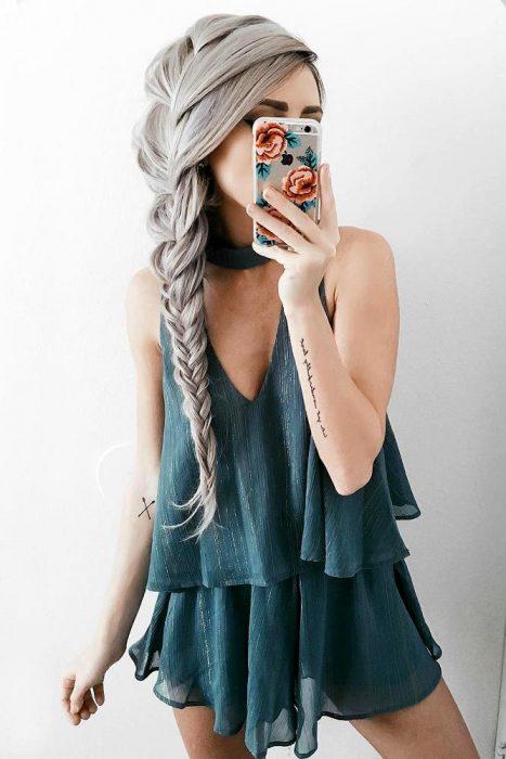 Chica de cabello largo y gris con una trenza y jumper verde