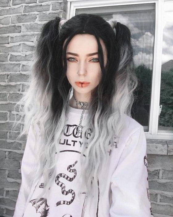 Chica de cabello largo de color negro y gris ondulado con dos coletas