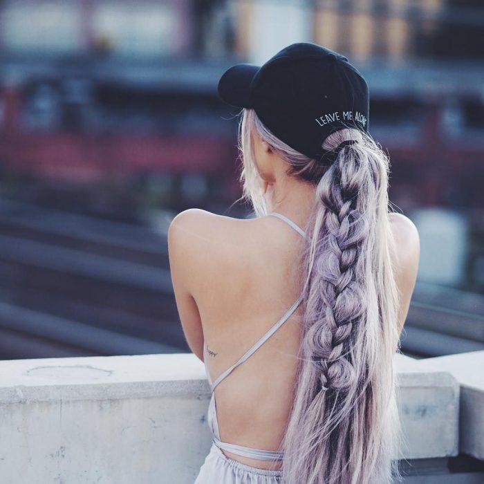 Chica de cabello color lila peinado con una trenza y usando gorra