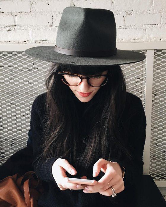 Chica con sombrero negro y lentes usando el celular