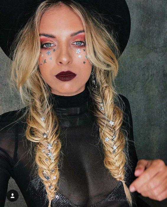 Chica con sombrero negro peinada con dos trenzas gruesas y diamantina