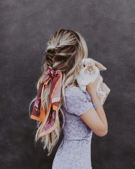 Chica rubia con trenza y bandana cargando a un conejo