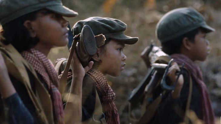 Escena de tres pequeños vestidos de soldados, entre ellos la pequeña actriz Sareum Srey Monch