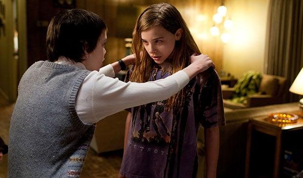 Chlöe Moretz en Let me in - chico deteniendo a una chica por los hombros
