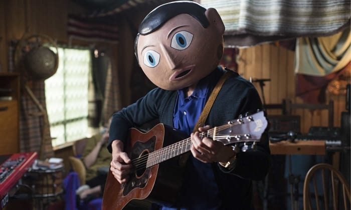 Chico usando máscara de papel tocando guitarra acústica