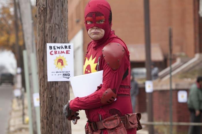 hombre usando ropa de superhéroe pegando carteles en árboles