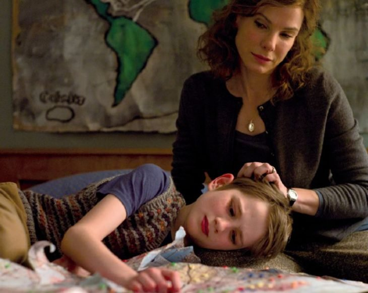 Sandra Bullock en escena de película Tan fuerte y tan cerca- mamá consolando a hijo pequeño que llora