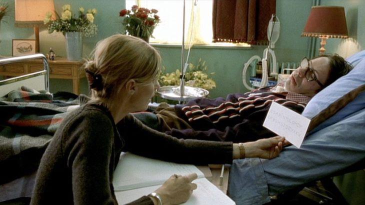 escena de la película El llanto de la mariposa - hombre parapléjico en cama con mujer que escribe