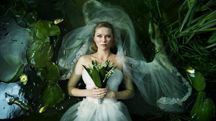 Kristen Dust para la película de Melancolía vestida de novia flotando sobre agua rodeada de plantas