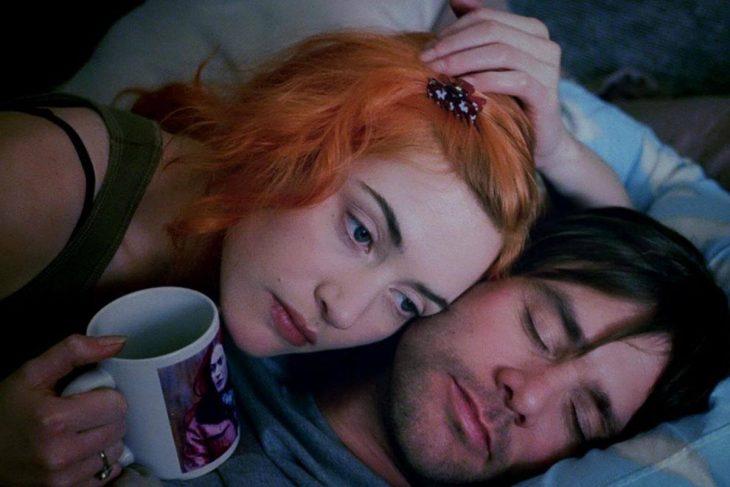 Kate Winslet y Jim Carrey en Eterno resplandor de una mente sin recuerdos - chica pelirroja con taza recostada junto a hombre dormido