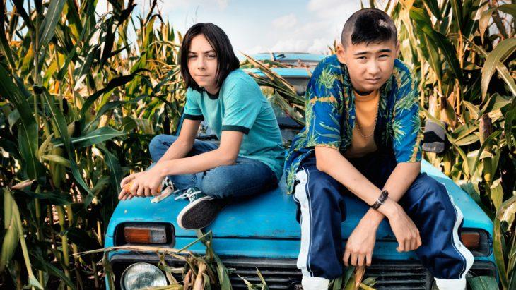 chicos sentados sobre un coche