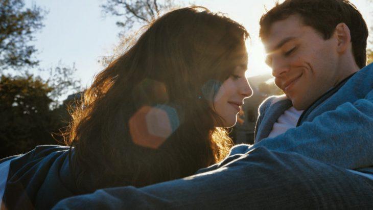 La actriz Lily Collins y el actor Sam Claflin sentados sobre el pasto en la cinta Tal vez es para siempre