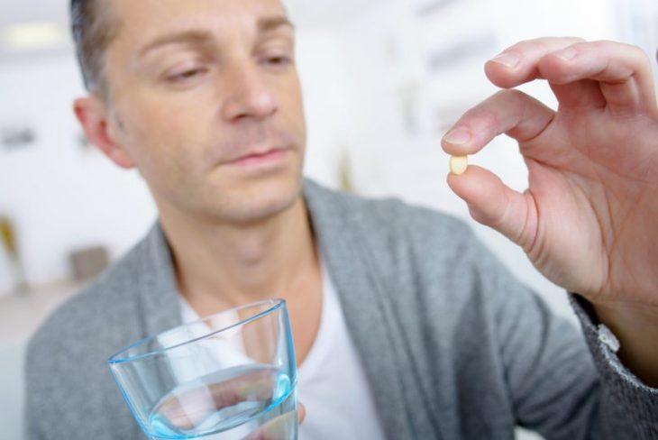 Hombre sosteniendo un vaso y una pastilla anticonceptivo masculino entre sus manos