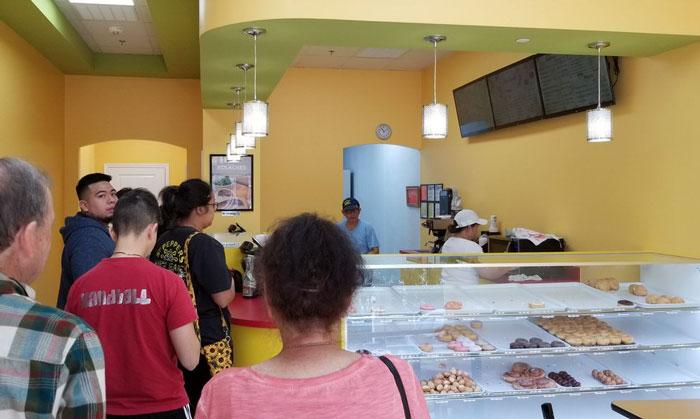 Personas haciendo fila para comer donas