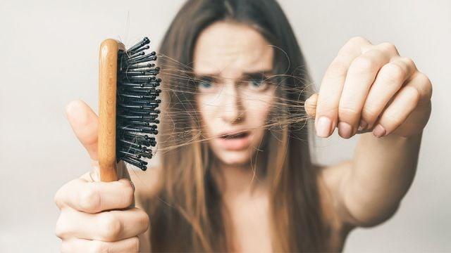 chica retirando el cabello de su cepillo