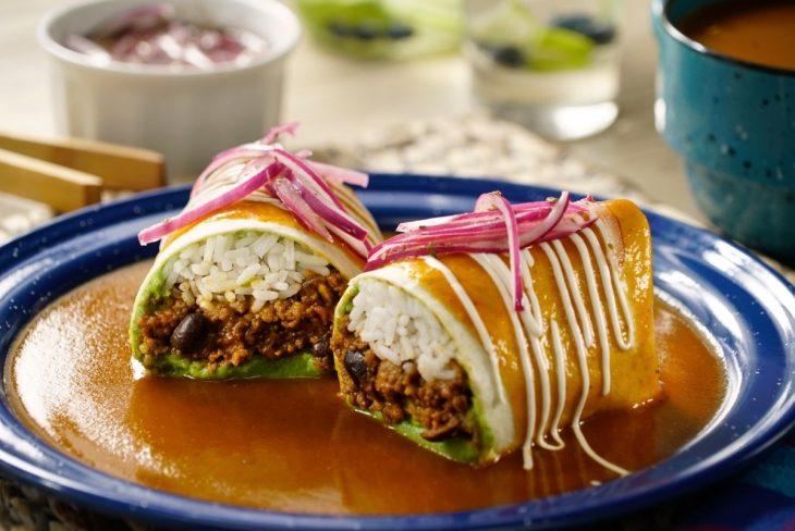 Burrito ahogado estilo mexicano relleno de arroz blanco, carne adobada y aguacate, cubierto de salsa de tomate, crema y cebolla morada