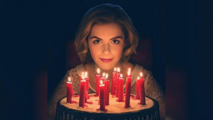 chica soplando las velas del pastel
