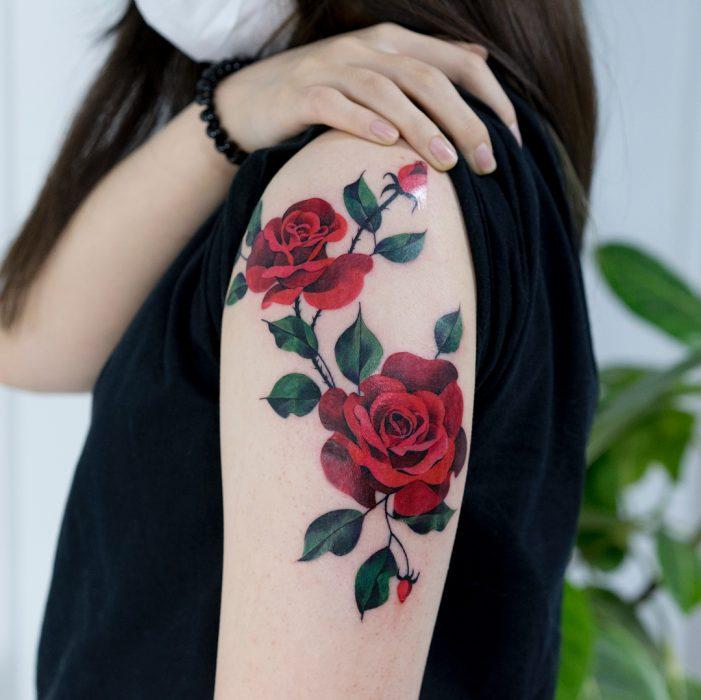 Tatuaje colorido de rosas rojas en el brazo