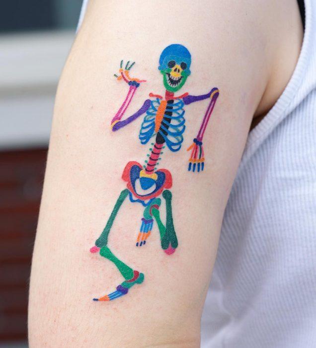 Tatuaje colorido de calavera en el brazo hecho por tatuadora coreana Zihnee