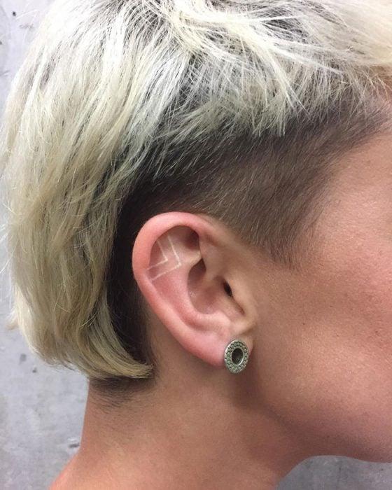 Tatuaje de tinta blanca en líneas rectas en parte superior de la oreja